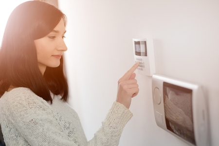 Photo for Young brunette woman entering code on keypad of home security alarm. Video intercom next to alarm keypad. - Royalty Free Image