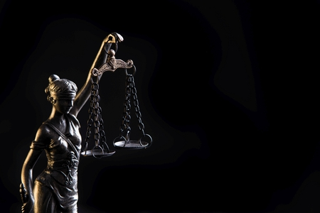 Foto de Statuette of the goddess of justice Themis with scales - isolated on black background. Law concept - Imagen libre de derechos