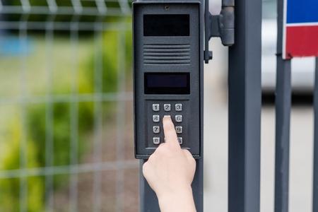 Foto de Little child boy pushes a button on the intercom mounted on the gate - Imagen libre de derechos