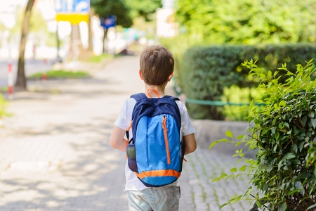 Photo pour Little 7 years schoolboy going to school. Dressed in white t shirt and shorts. Blue backpack - image libre de droit