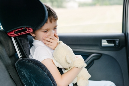 Foto de Seven years old small child in the backseat of a car sitting in children safety car seat covers his mouth with his hand - suffers from motion sickness - Imagen libre de derechos