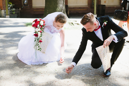Photo for Newlyweds collects coins thrown by the wedding guests. Wedding day - Royalty Free Image
