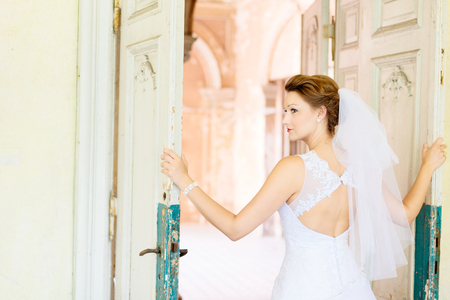Photo for Young beautiful bride in white dress near old door . Wedding day. Wedding session - Royalty Free Image