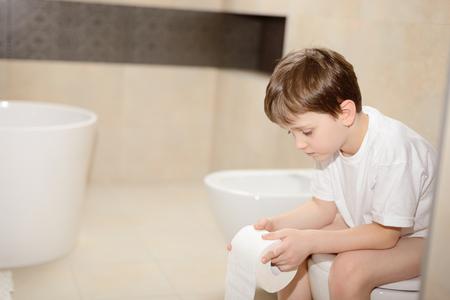 Foto de Little 7 years old boy sitting on toilet. Holding white toilet paper - Imagen libre de derechos