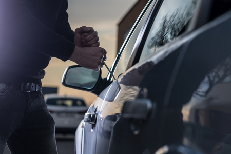 Foto per Auto thief in black balaclava trying to break into car with screwdriver. Car thief, car theft - Immagine Royalty Free