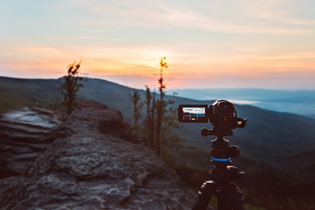 Photo for Digital video camera on tripod filming sunrise at mountains. Silesian Beskid, Poland - Royalty Free Image