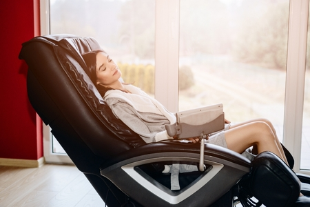 Foto de Young woman relaxing on the massaging chair at home - Imagen libre de derechos