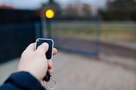 Photo pour Man opening automatic property gate with remote controller - image libre de droit