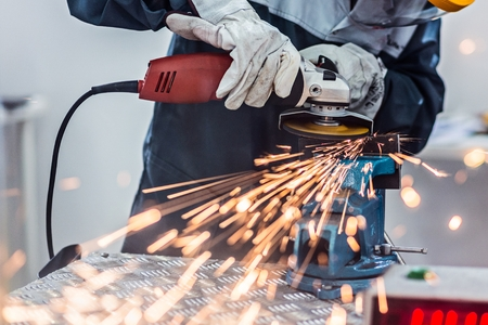 Photo for Worker cutting metal with angle grinder. Metalwork in factory - Royalty Free Image