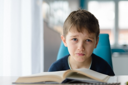 Photo for Tired 8 years old boy doing his homework at the table. Child reading a book at the desk. - Royalty Free Image