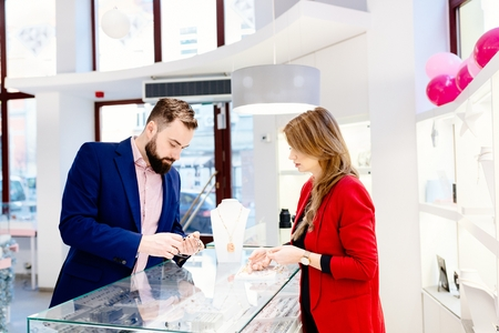 Photo for Beauty female seller presents a necklace. Jewelry store. Woman jeweler. Attractive man with a beard choosing a valentine's day gift in jewelry store - Royalty Free Image