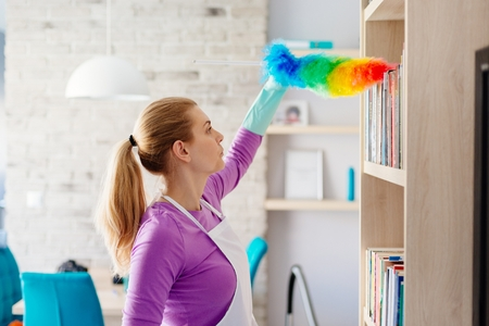 Photo pour Young beautiful woman in white apron dusting books. Cleaning service. Maid cleaning at home - image libre de droit