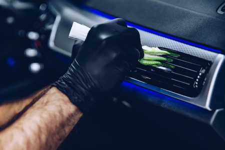 Foto de Man worker in car wash cleaning car air vent. Car detailing - Imagen libre de derechos