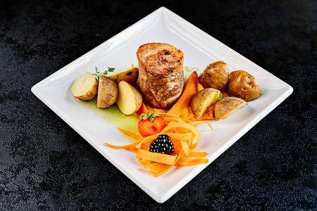 Foto de Roaster pork with potatoes on white plate - Imagen libre de derechos