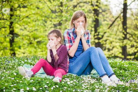 Foto de Two people with allergy symptom blow their noses - Imagen libre de derechos