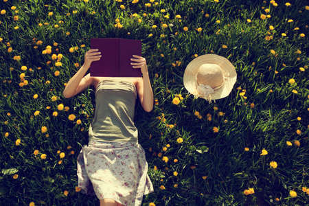 Photo pour Girl lying in grass reading a book. Intentionally toned. - image libre de droit