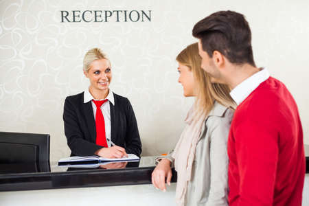 Photo for Young couple check in at hotel reception - Royalty Free Image