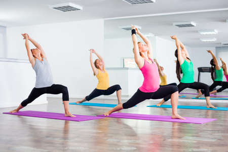 Photo pour Four girls practicing yoga, Yoga - VirabhadrasanaWarrior pose - image libre de droit