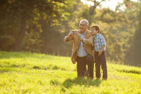 Foto de Grandfather and grandson photographing nature in park - Imagen libre de derechos