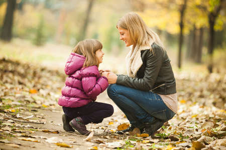 Photo pour Happy mother and daughter having fun in park in autumn - image libre de droit