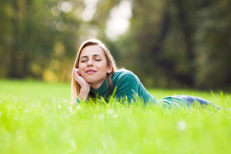 Happy woman relaxing and enjoying nature in park