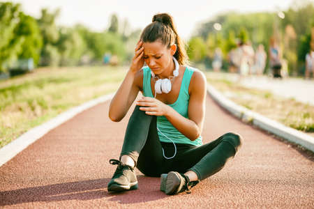 Photo for Young woman got injured while jogging on sunny day. - Royalty Free Image