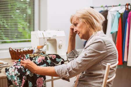 Photo pour Adult woman is sewing in her studio. She is frustrated because she made a mistake. - image libre de droit