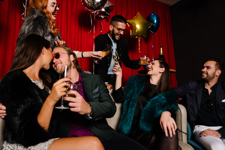 Photo pour Couple kissing at a party with people toasting in background - image libre de droit