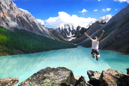Photo pour Beautiful mountain landscape with the lake and the jumping man  - image libre de droit