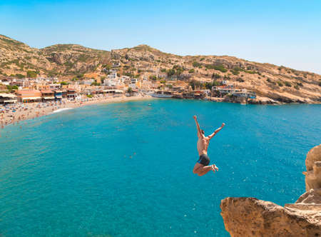 Foto de Extreme sports. Young man jumping from the cliff in the sea. - Imagen libre de derechos