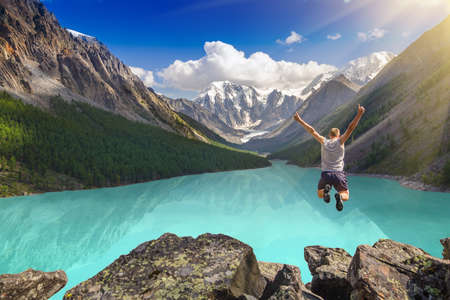 Foto de Beautiful mountain landscape with lake and jumping man - Imagen libre de derechos