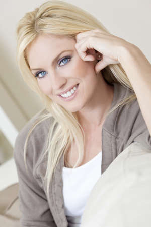 Natural light portrait of a beautiful blond woman with blue eyes resting on her sofa at home