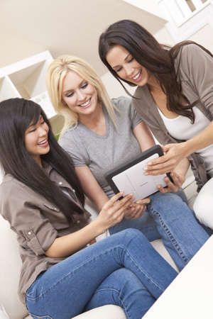 Three beautiful young women friends at home using tablet computer and laughing