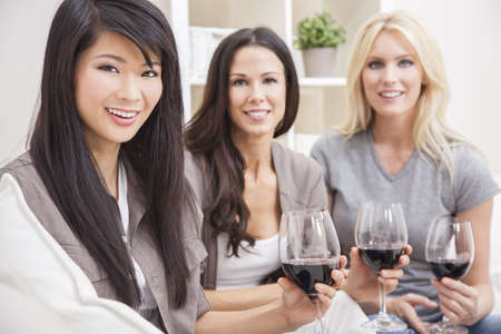 Interracial group of three beautiful young women friends at home drinking red wine together