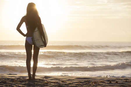 Photo for Rear view of beautiful sexy young woman surfer girl in bikini with white surfboard on a beach at sunset or sunrise - Royalty Free Image