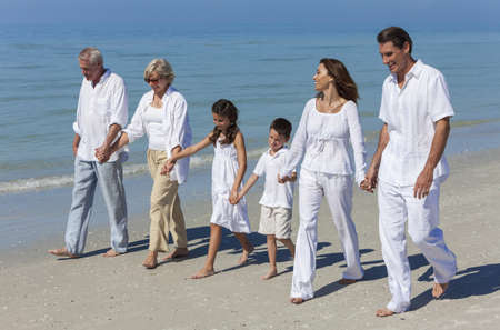 Photo pour A happy family of grandparents, mother, father and two children, son and daughter, walking holding hands and having fun in the sand of a sunny beach - image libre de droit