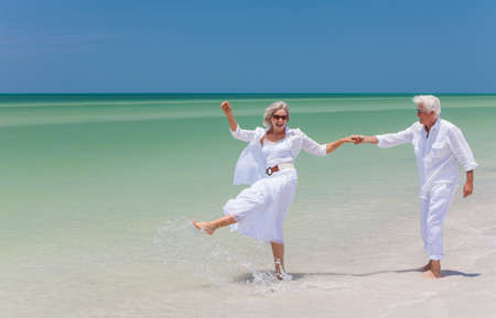 Foto de Happy senior man and woman couple dancing, holding hands & splashing in sea water on a deserted tropical beach with bright clear blue sky - Imagen libre de derechos