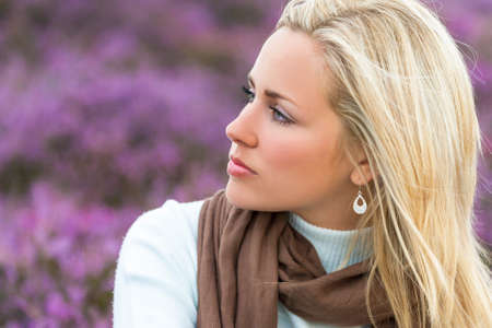 A naturally beautiful young blond woman in a field of purple heather flowers
