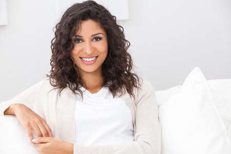 Foto de Portrait of a beautiful young Latina Hispanic woman smiling with perfect teeth sitting on a white sofa - Imagen libre de derechos