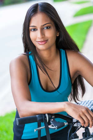 Foto de Outdoor fitness portrait of a beautiful Indian Asian young woman or girl outside in summer sunshine riding cycling her bicycle - Imagen libre de derechos