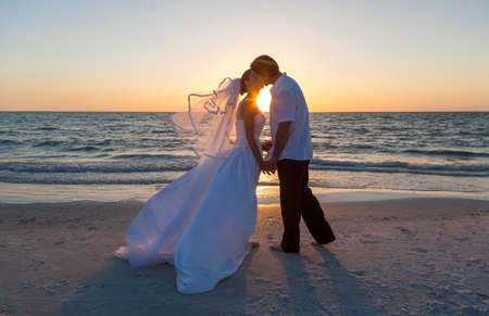 Photo pour A married couple, bride and groom, kissing at sunset or sunrise on a beautiful tropical beach - image libre de droit