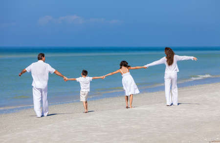 Photo pour Rear view of happy family of mother, father and two children, son and daughter, walking holding hands and having fun in the sand on a sunny beach - image libre de droit