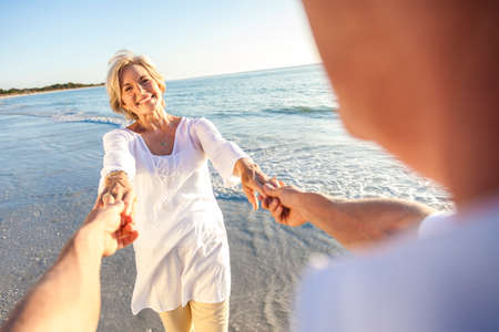 Photo pour Happy senior man and woman couple walking or dancing and holding hands on a deserted tropical beach with bright clear blue sky - image libre de droit