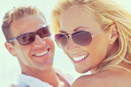 Foto de photograph of happy and attractive man and woman couple wearing sunglasses and smiling in sunshine at the beach - Imagen libre de derechos