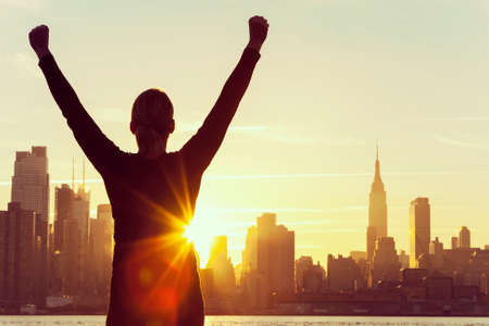 Foto de  silhouette of a successful woman or girl arms raised celebrating at sunrise or sunset in front of the New York City Skyline - Imagen libre de derechos
