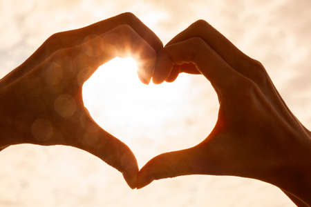 Foto de Hand heart shape silhouette made against the sun & sky of a sunrise or sunset - Imagen libre de derechos