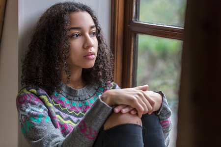 Foto de Beautiful mixed race African American girl teenager female young woman sad depressed or thoughtful looking out of a window - Imagen libre de derechos