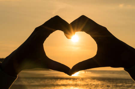 Photo pour Hand heart frame shape silhouette made against the sun & sky of a sunrise or sunset on a deserted empty beach - image libre de droit