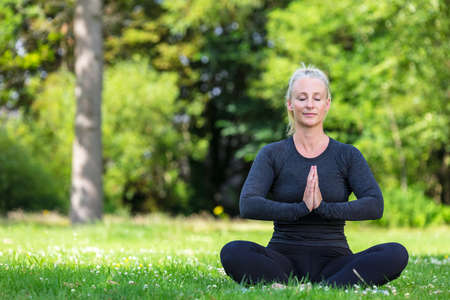 Photo pour Mature middle aged fit healthy woman practicing yoga outside in a natural tranquil green environment - image libre de droit