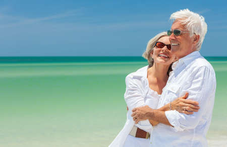 Photo pour Happy laughing senior man and woman retired couple embracing wearing sunglasses on a deserted tropical beach with turquoise sea and clear blue sky - image libre de droit
